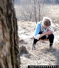 Young blonde squats to pee secretly in a forest
