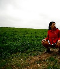 Barely legal brunette tinkling alone on a field