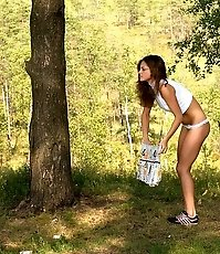 Sexy slim nature-admirer whizzing under a tree