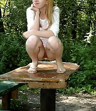 Prankish babe pisses onto a table in the park